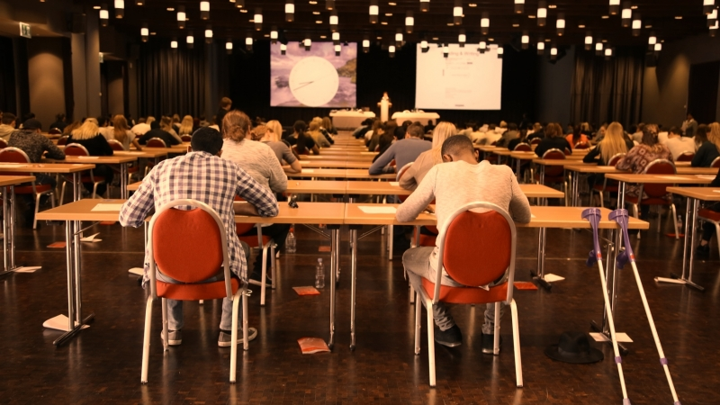 A venue full of students sitting on red chairs taking their paper-based Cambridge English exam. Lights make the room look bright a poweroint presentation is shown in the front with informaiton about the exam and the time left for th exam.
